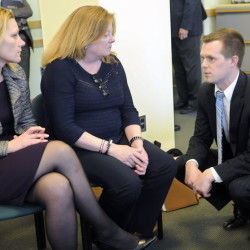 Volunteers of America staff Melissa Morrill, left, and Julia Wilcock speak with Rep. Jared Golden, D-Lewiston, on Thursday about his bill to help their cause in creating housing for homeless veterans at the VA Maine Healthcare Systems-Togus campus near Augusta.
