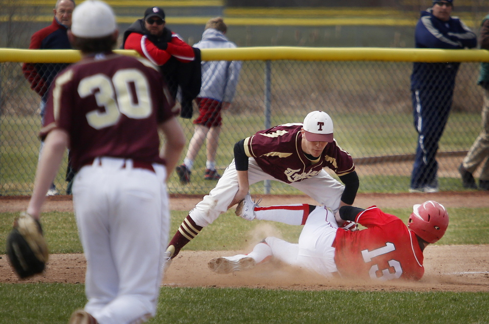 Thornton Academy third baseman Mitch Jacques tags out South Portland's Henry Curran on a stolen-base attempt.