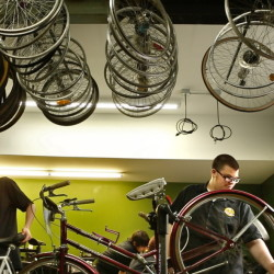 From left, Devyn Hibbard, Connor Oliver and Matt Perkins work on bicycles at the Community Bicycle Center. The program teaches teens to fix the bikes but also focuses on marketing and customer service lessons.