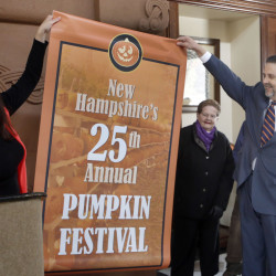 Ed Engler, right, the mayor of Laconia, N.H., helps unroll a poster Friday announcing the city as the new host of the annual Pumpkin Festival. Held in Keene since 1991, the family-friendly event was marred by arrests last year, many of them college students.