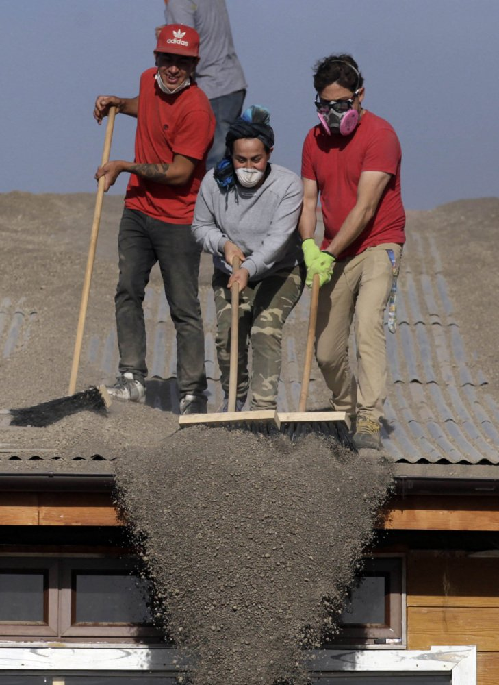 People sweep volcanic ash from a home's roof in Puerto Varas, Chile, on Friday.