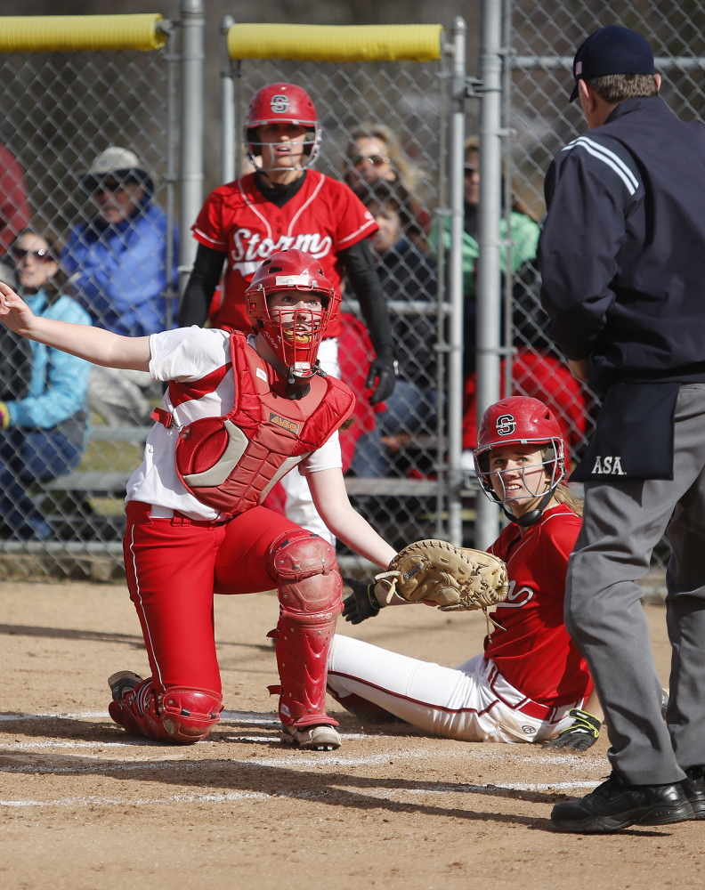 South Portland catcher Kiley Kennedy and Kaleigh Scoville of Scarborough wait for the call on a close play at the plate Friday. Scoville was called out, but Scarborough won the mutual season opener, 26-0 in five innings.