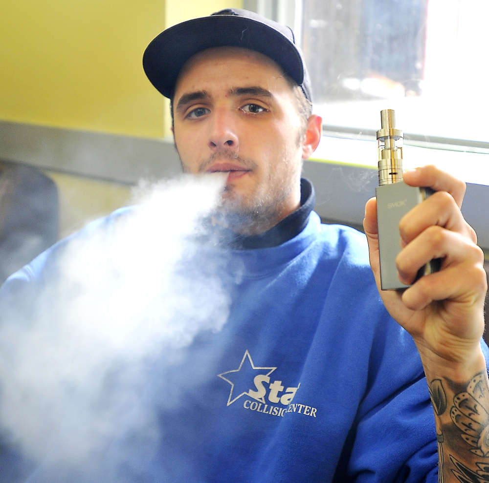 Richard Gadourey uses his vaporizer in the Old Port Vape Shop on Market Street. Portland is evaluating an ordinance that treats vaporizers like cigarettes.