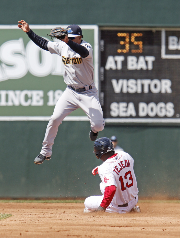 Oscar Tejeda of the Portland Sea Dogs slides safely into second base with a steal Saturday as Jose Rosario of the Trenton Thunder leaps for the catch during the second inning of the Sea Dogs' 7-3 victory at Hadlock Field.