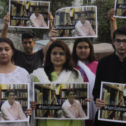 "Members of the social group ""Umeed Jawan Peace Society"" hold pictures of Sabeen Mahmud, who was killed Friday by unknown gunmen."