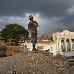 A Nepalese policeman stands atop of a rubble at Basantapur Durbar Square on Sunday that was damaged in Saturday's earthquake in Kathmandu, Nepal.