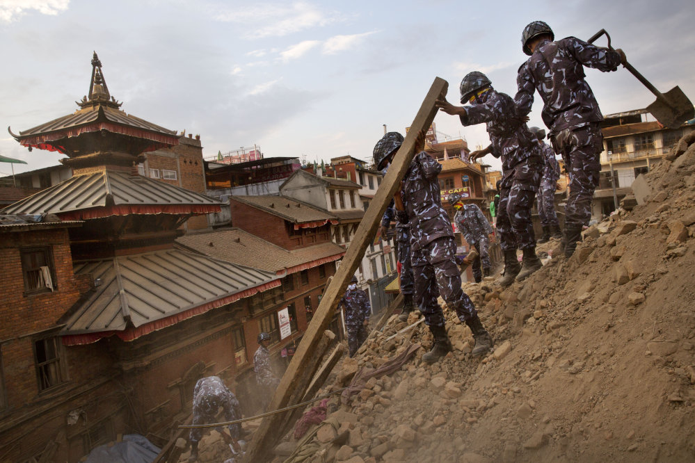 Nepalese policemen clear the debris at Basantapur Durbar Square, damaged in Saturday's earthquake, in Kathmandu, Nepal, on Sunday.