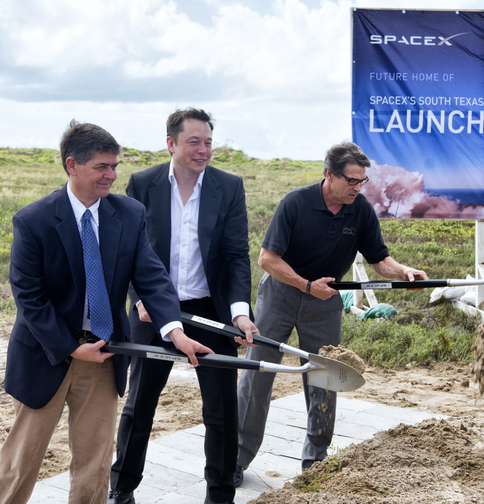 Texas Rep. Filemon Vela, left, SpaceX founder and CEO Elon Musk, center, and Texas Gov. Rick Perry turn the first shovels of sand at the groundbreaking ceremony for the SpaceX launch pad at Boca Chica Beach, Texas, in 2014.