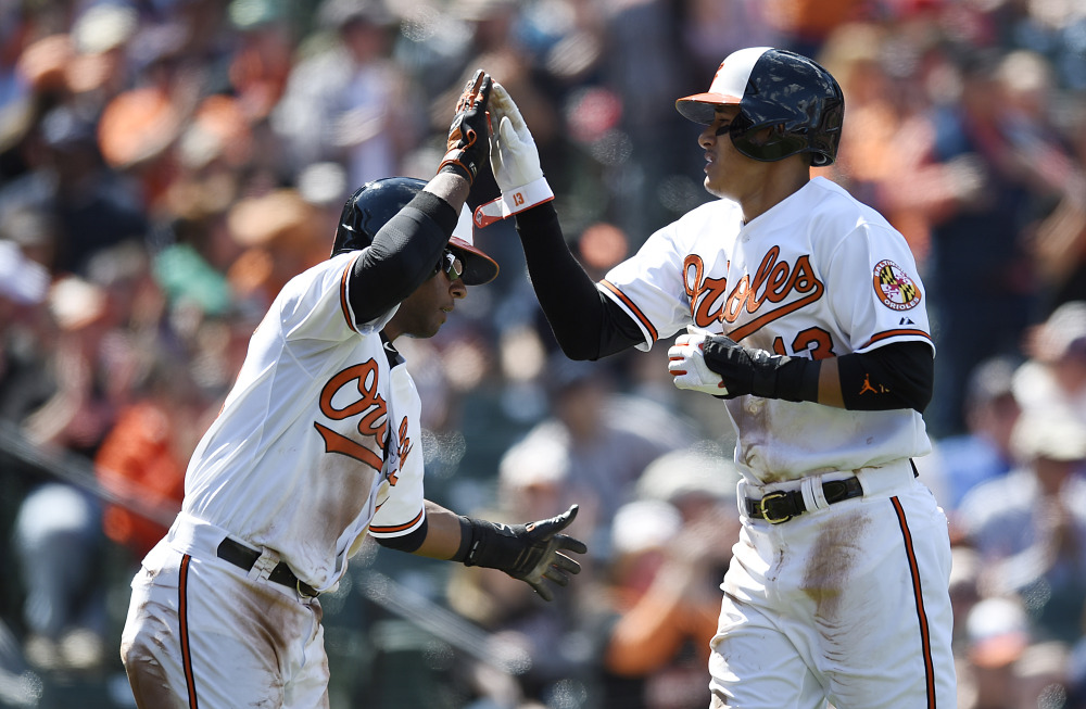 Baltimore Orioles Manny Machado, right, and Rey Navarro celebrate after scoring on a Delmon Young single against Boston Red Sox in the fourth inning  Sunday in Baltimore.