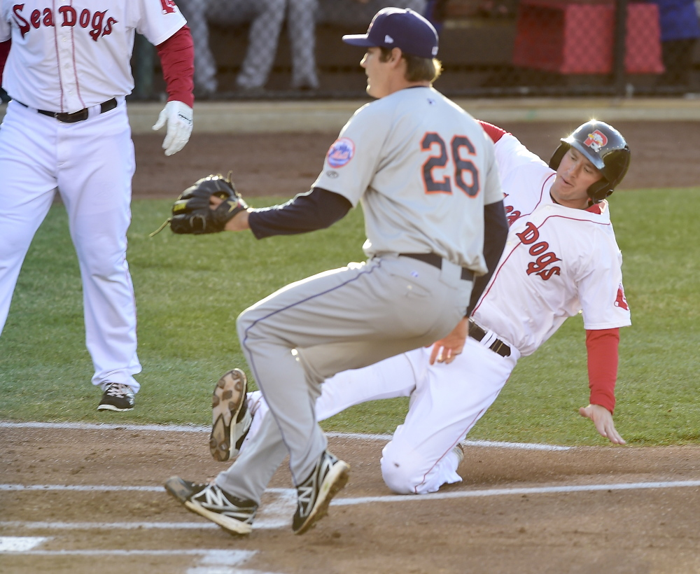 Portland's Keury De La Cruz slides home on a passed ball for the Sea Dogs' first run as Mets pitcher Seth Lugo awaits the ball. (Gordon Chibroski/Staff Photographer)