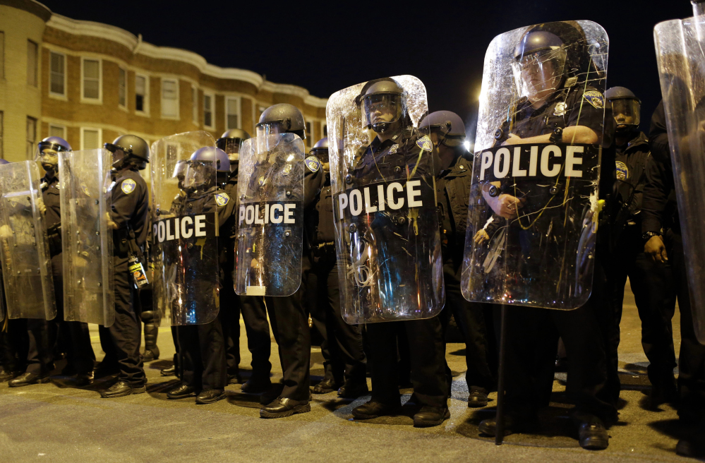 Police stand in formation as a curfew approaches Tuesday night in Baltimore, a day after rioting that followed Freddie Gray's funeral.
