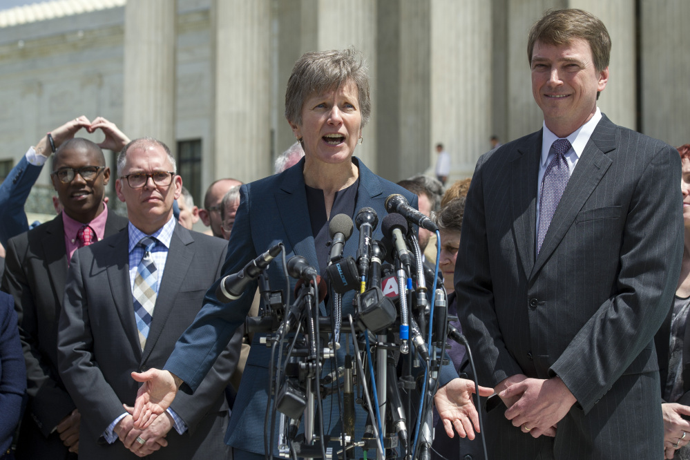 Plaintiff James Obergefell of Ohio, left, and Washington attorney Douglas Hallward-Driemeier, right, listen as civil rights lawyer Mary Bonauto, center, speaks with reporters outside the Supreme Court in Washington on Tuesday following the court's hearing on same-sex marriage.
