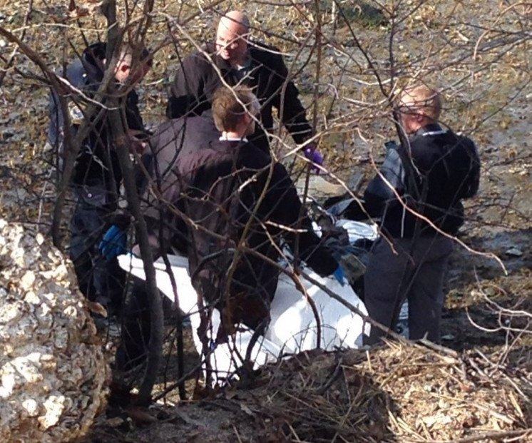 Police examine the body that was found Tuesday afternoon on the shore of the Fore River in South Portland.