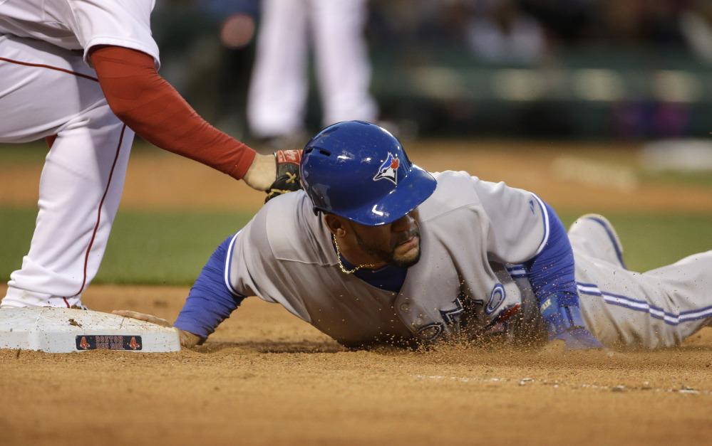 Toronto Blue Jays' Devon Travis, right, jumps back to first base to survive a pick-off attempt in the fourth inning as Boston's Daniel Nava tries to tag him. (AP Photo/Steven Senne)