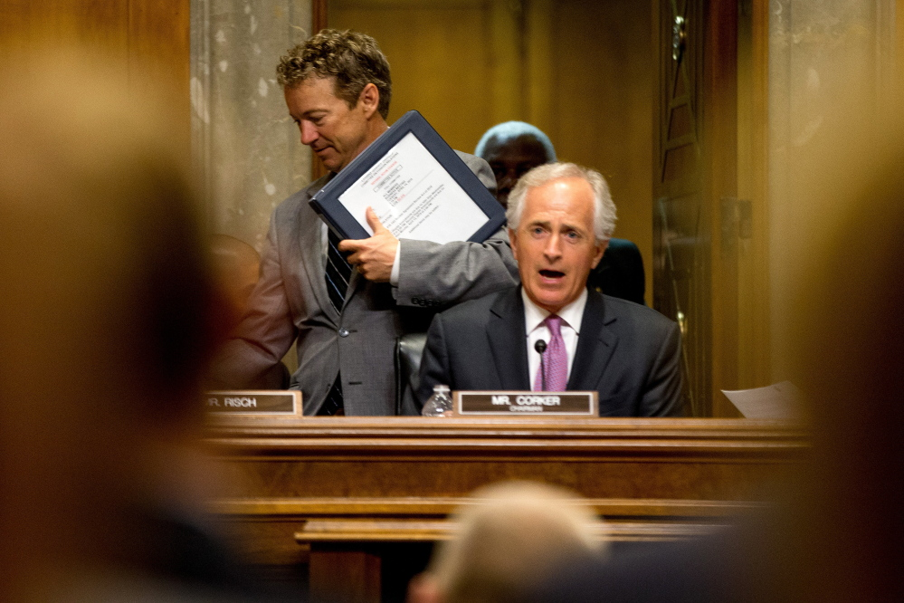 Republican Presidential candidate,and Senate Foreign Relations Committee member, Sen. Rand Paul, R-Ky, left, passes Committee Chairman Sen. Bob Corker, R-Tenn., on Capitol Hill in Washington, Tuesday, April 14, 2015, during the committee'smeeting to debate and vote on the Iran Nuclear Agreement Review Act of 2015. Republican and Democrats on the Senate Foreign Relations Committee reached a compromise Tuesday on a bill that would give Congress a say on an emerging deal to curb Iran's nuclear program. (AP Photo/Andrew Harnik)