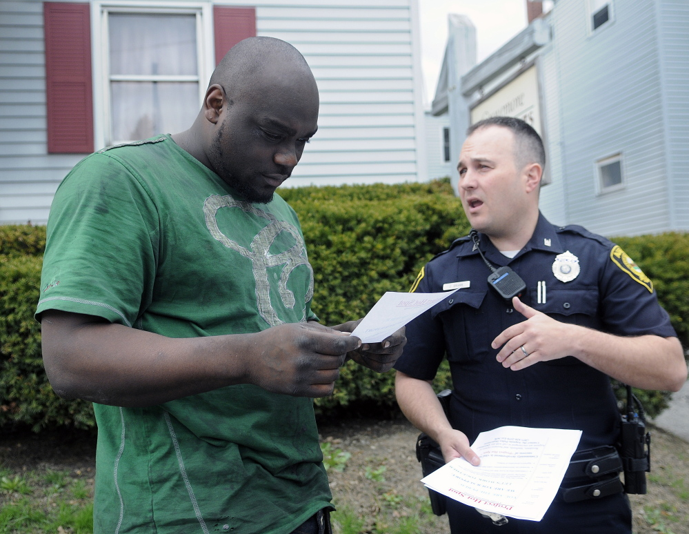 Augusta Police Officer Jesse Brann speaks with Water Street resident Breon Shannon on Wednesday while handing out fliers to notify people of a larger police presence planned. Shannon said he sees a lot of drug-related crime in the neighborhood. Police spread out across Augusta to hand out the information while soliciting input on how to combat crime.