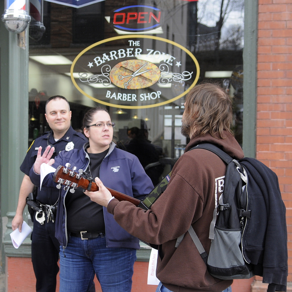 "Augusta Police Detective Tori Tracy and Officer Jesse Brann speak with a man Wednesday playing guitar on Water Street while canvassing. Law enforcement officers were notifying people of a larger police presence planned in crime ""hot spots"" while soliciting information on how to combat crime."