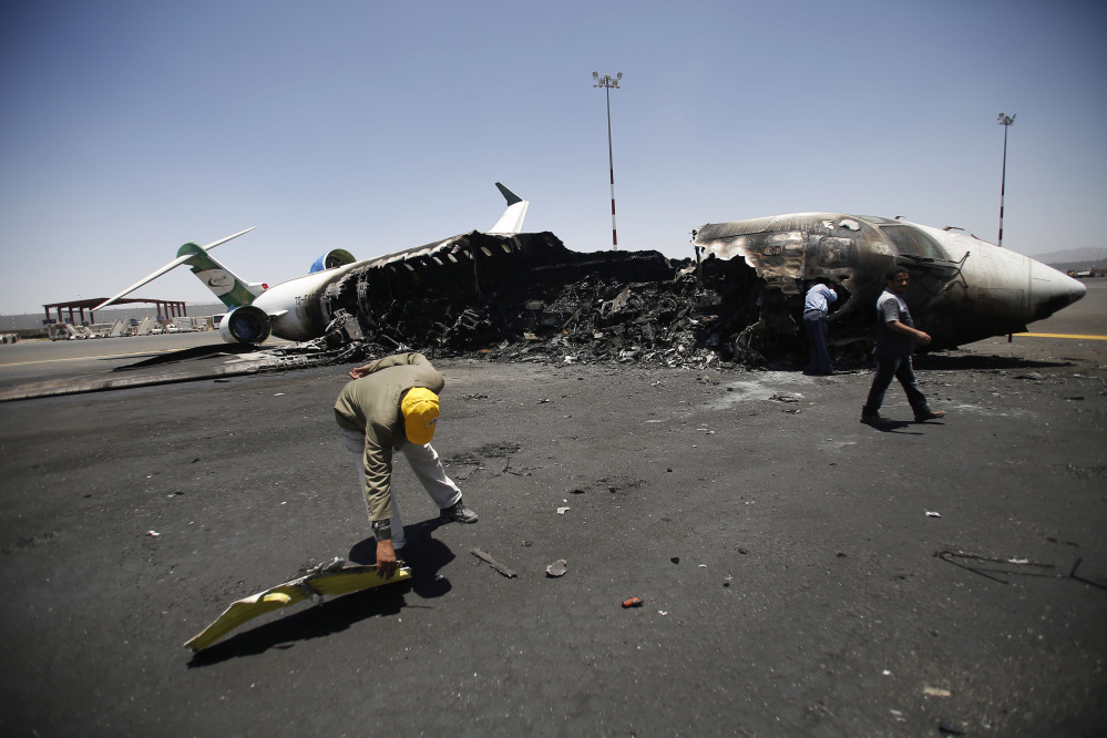 Officials of Felix Airways, a domestic airline, inspect a plane destroyed by Saudi-led airstrikes, at the Sanaa International Airport, in Yemen, on Wednesday. Saudi-led coalition warplanes pounded Shiite rebels and their allies overnight and throughout the day on Tuesday in the Yemeni capital. Around midday, airstrikes hit Sanaa International airport, setting a plane owned by a private company on fire, according to a statement released by the Houthis.