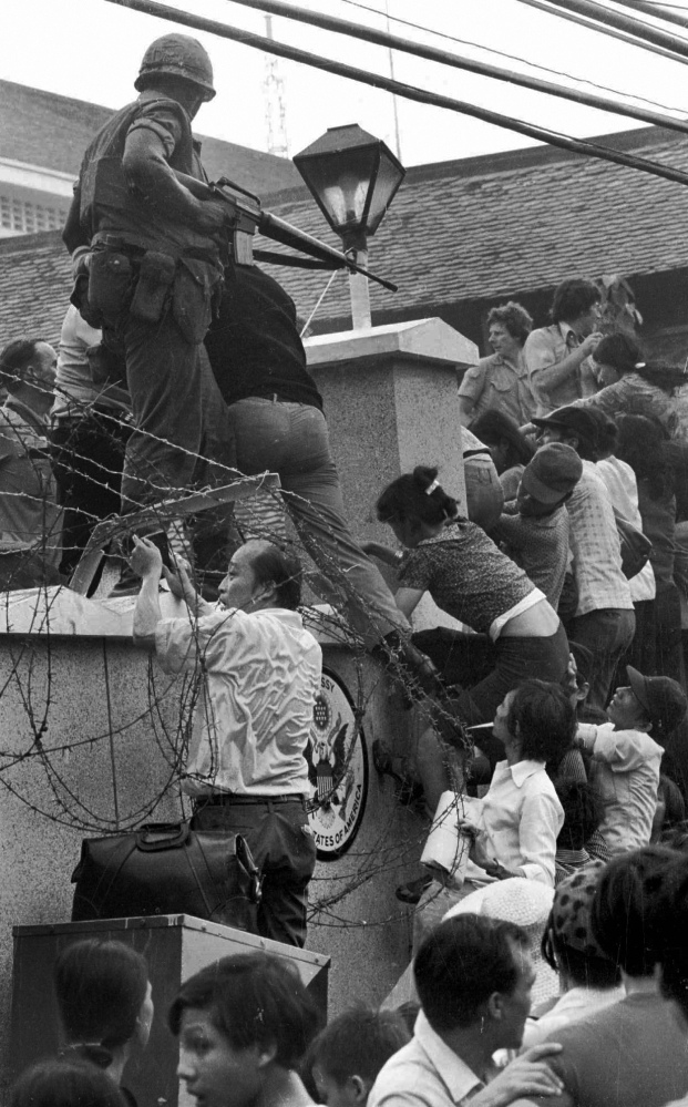 On April 29, 1975, people scale the 14-foot wall of the U.S. embassy in Saigon, trying to reach evacuation helicopters, as the last of the Americans depart from Vietnam.
