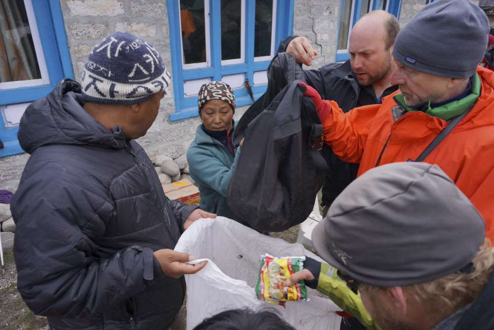 Doug Bruns, right, and fellow trekkers, hand out tarps and food Wednesday to residents of Thame, Nepal, a remote mountain village that was leveled by Saturday's earthquake. Photo by Rick Nooft