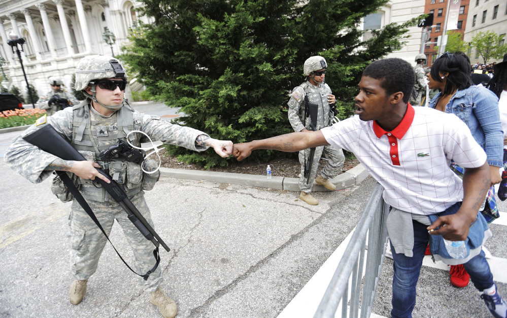 Brandon Payton, right, of Baltimore, fist-bumps a National Guardsman standing outside City Hall as protesters march by to demonstrate the police-custody death of Freddie Gray on Thursday in Baltimore. Baltimore police say they have turned over their criminal investigation to a prosecutor who will decide whether charges are warranted in the death of Gray.