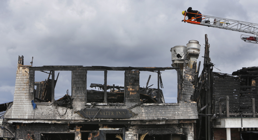 Perched on a ladder of an Ogunquit Fire Department truck, an investigator with the state Fire Marshal's Office takes a photo of the Blue Water Inn in Ogunquit on Wedensday, the day after a windswept fire destroyed the building.
