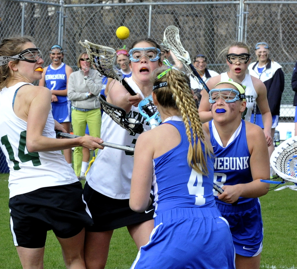 Waynflete's Christian Rowe, center, vies for the ball against  Kennebunk's Molly Parent, front right, and Hannah Pepin.