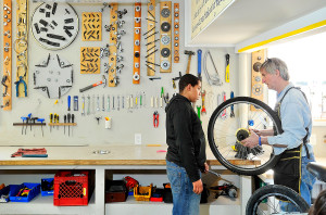 Javier Stokes, 13, left, gets training from Executive Director Andy Greif at the Community Bicycle Center in Biddeford. The larger facility allows for tool display on the walls and plenty of space for the kids to fix bikes and learn life lessons like courtesy, responsibility, hard work and problem solving, according to Greif.