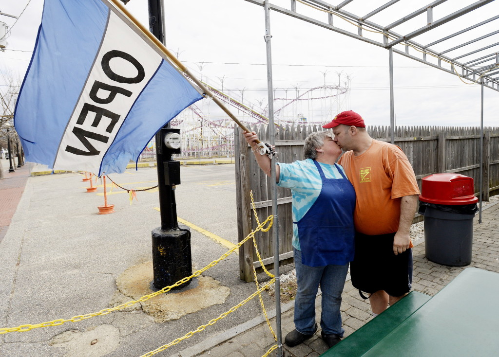 "Brian Coddens (Hoss) gives a kiss to Deena Eskew (Mary) as they put up the ""open"" flag for the last time in 2015 at their restaurant in Old Orchard Beach."