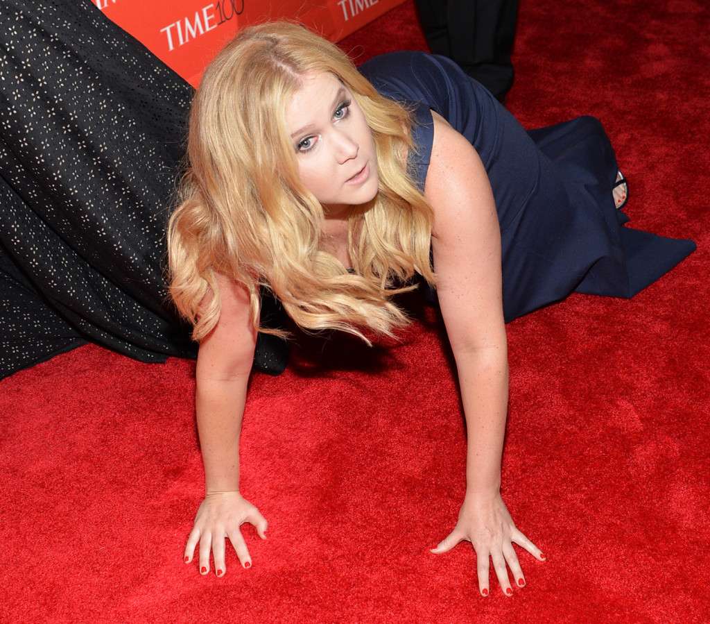 Comedian Amy Schumer takes a well-timed pratfall on the red carpet in front of Kim Kardashian and Kanye West at a TIME  gala on April, 21, 2015. Invision photo via AP
