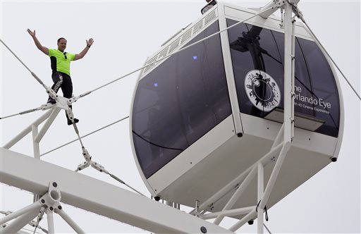 Daredevil performer Nik Wallenda waves to a crowd below after he walked untethered along the rim of the Orlando Eye, the city's new, 400-foot observation wheel, Wednesday in Orlando, Fla.
