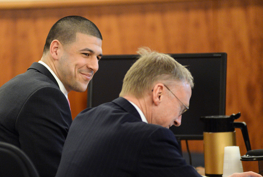 Former New England Patriots tight end Aaron Hernandez smiles with attorney Charles Rankin in the courtroom during the jury's first full day of deliberations in Hernandez' murder trial, on April 8. The Associated Press