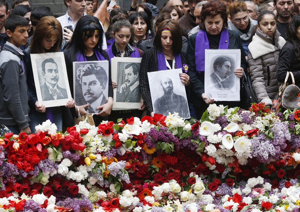 People lay flowers at a memorial to Armenians killed by the Ottoman Turks, as they mark the centenary of the mass killings, in Yerevan, Armenia, Friday. The Associated Press
