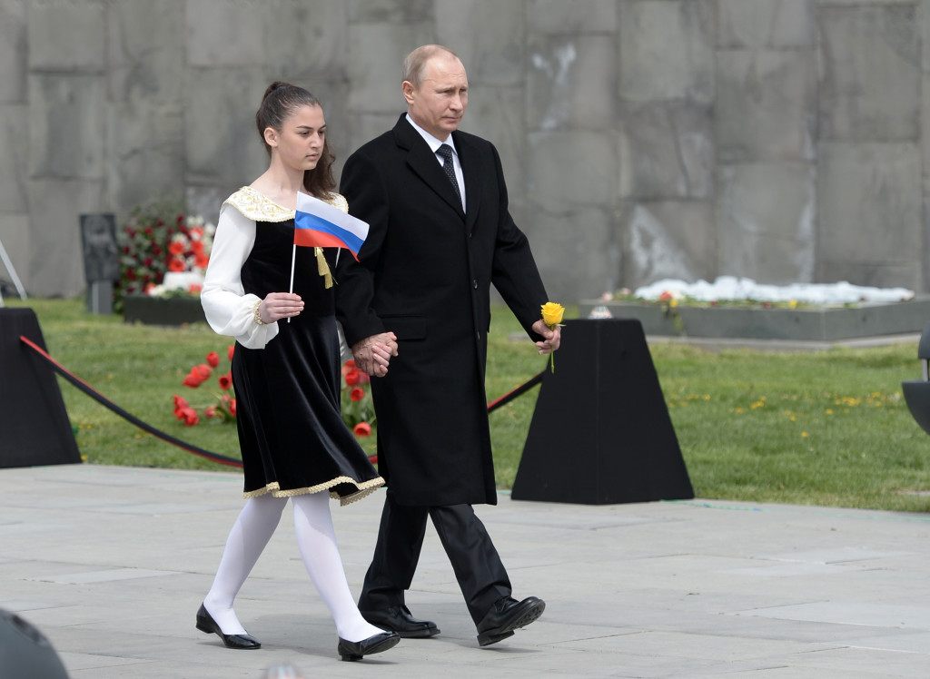 Russian President Vladimir Putin, escorted by a girl holding a Russian flag, walks at the Tsitsernakaberd Armenian Genocide memorial complex in Yerevan, Armenia, Friday. He is among world leaders attending ceremonies commemorating the massacre of Armenians by Ottoman Turks. The Associated Press