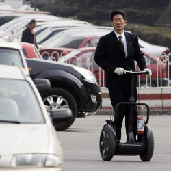A man takes a Segway on a practice run in a parking lot in Beijing. The Associated Press