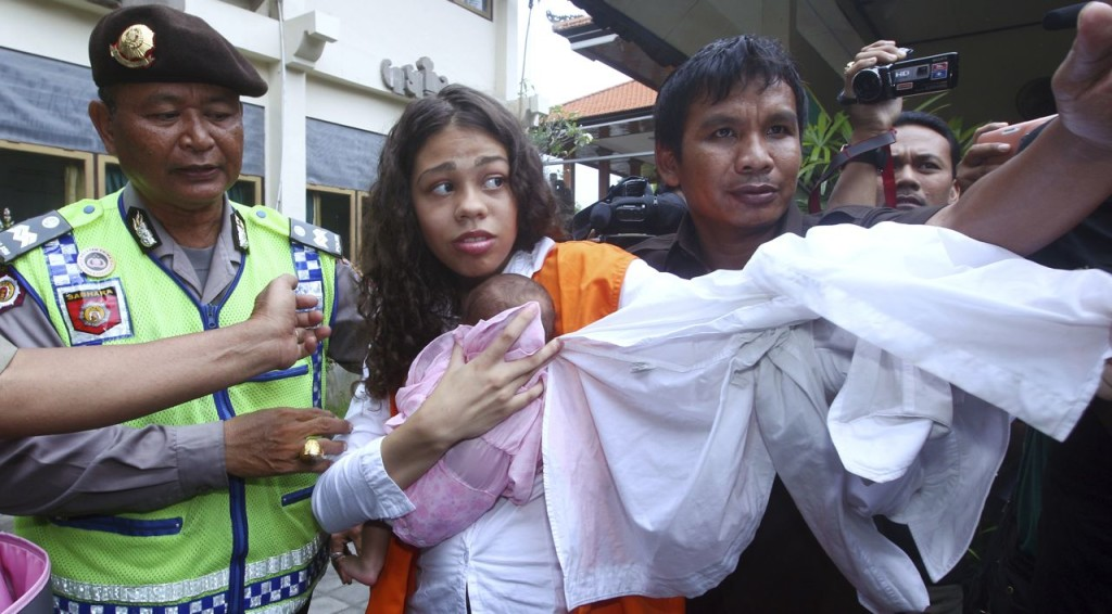 Heather Mack of Chicago carries her baby daughter as she arrives at the Denpasar District Court before the verdict was read Tuesday in her trial in Bali, Indonesia. The Associated Press