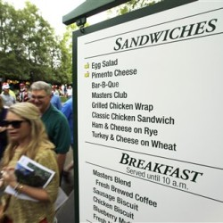 In this file photo taken Monday, April 6, 2015, patrons walk past a vendor sign during a practice round for the Masters golf tournament, in Augusta, Ga. At a time when buying a hot dog and a beer at any big event can mean a pricey tab and a credit card, Augusta National makes it easy to fill up in possibly the best value meal deal in all of sports with a menu that is pure South. The Associated Press