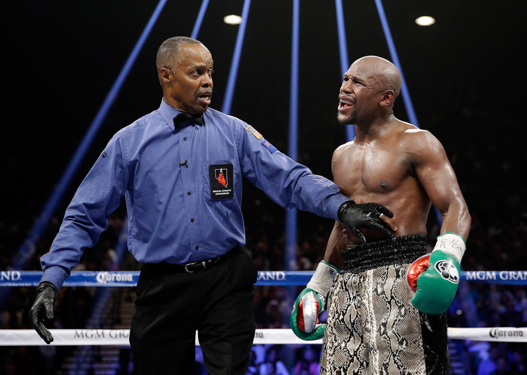 Boxer Floyd Mayweather, shown speaking to referee Kenny Bayless, has proved a smart businessman by signing for a fight that will earn him $180 million or more.