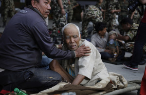 A Nepalese man attends to an elderly as victims of Saturday's earthquake, wait for ambulances after being evacuated at the airport in Kathmandu, Nepal, Monday. The Associated Press
