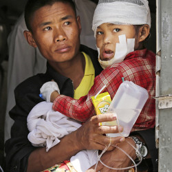 A Nepalese soldier holds a child injured in Saturday's earthquake as they wait to disembark from an Indian Air Force helicopter at the airport in Kathmandu Monday. The Associated Press