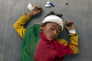 An injured boy sleeps outside the overcrowded Dhading hospital in the aftermath of Saturday's earthquake in Nepal Monday. Reuters