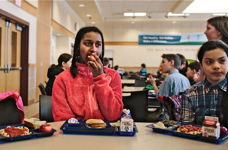Shurube Stamey, a fifth-grader at Westbrook Middle School, enjoys a piece of fruit at lunchtime. Whitney Hayward / Staff Photographer