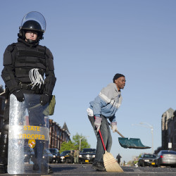 Residents clean streets as law enforcement officers stand guard, Tuesday. The Associated Press