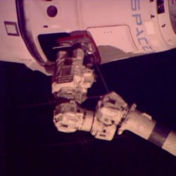 A robotic arm from the space station connects with the SpaceX Dragon freighter with its delivery of groceries, equipment and experiments.