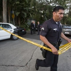 A police officer creates a perimeter outside the home of Andrew Getty  in the Hollywood Hills area of Los Angeles Tuesday. The Associated Press