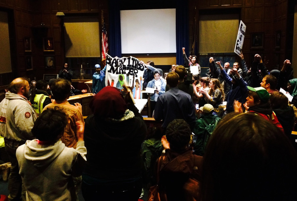 """Protesters chant """"black lives matter"""" while occupying the council chambers at Portland City Hall on Thursday night. Erin Hennessy, seen speaking in the center, said, """"I've rubbed my eyes red. How many more Michael Browns? How many more Trayvon Martins? .... We need a new definition of justice."""""""