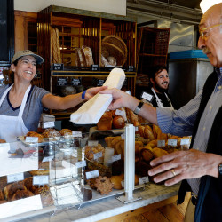 Standard Baking Co. employee Jill Finberg hands Harvey Rosenfeld a baguette, his favorite treat.