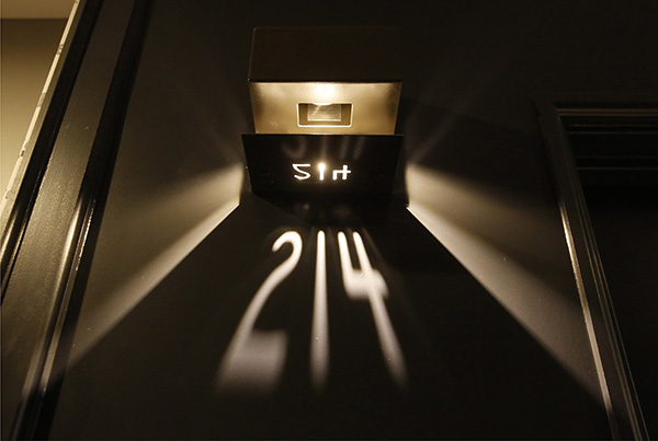 Room numbers at The Press Hotel shine on walls from light passing through the numbers cut out in a metal plate in this May 4, 2015 photograph of the newly-renovated hotel.