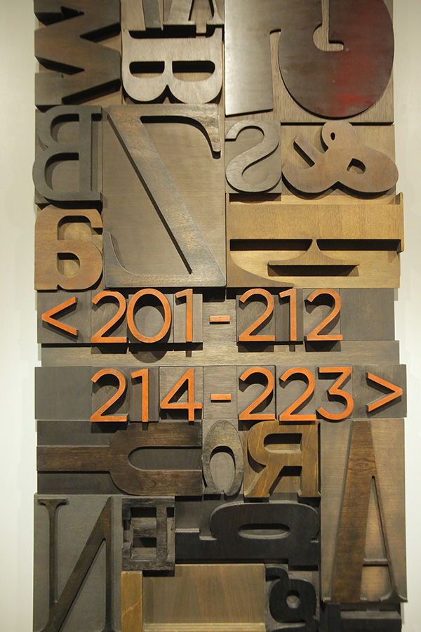 The room number directions in the hallways at The Press Hotel are designed with woodblock letters to recall the type once used to print newspapers. The woodblock carvings were created by Matt Hutton, an associate professor at Maine College of Art.