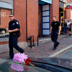 Portland police officers walk past flowers placed on the car that Treyjon Arsenault was driving Monday night before he was killed in a shooting at 26 Market St. in the Old Port. Police continued to investigate at the scene Wednesday. Gabe Souza/Staff Photographer